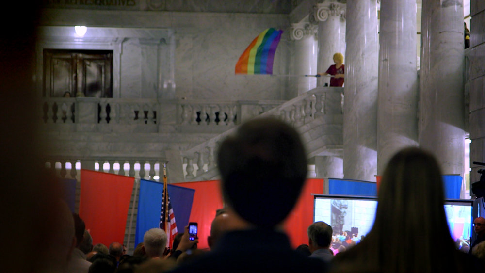 "A gay-rights protester flies a rainbow flag over a rally for ""traditional marriage,"" in a scene from the documentary ""Church & State."" (Photo courtesy Blue Fox Entertainment)"