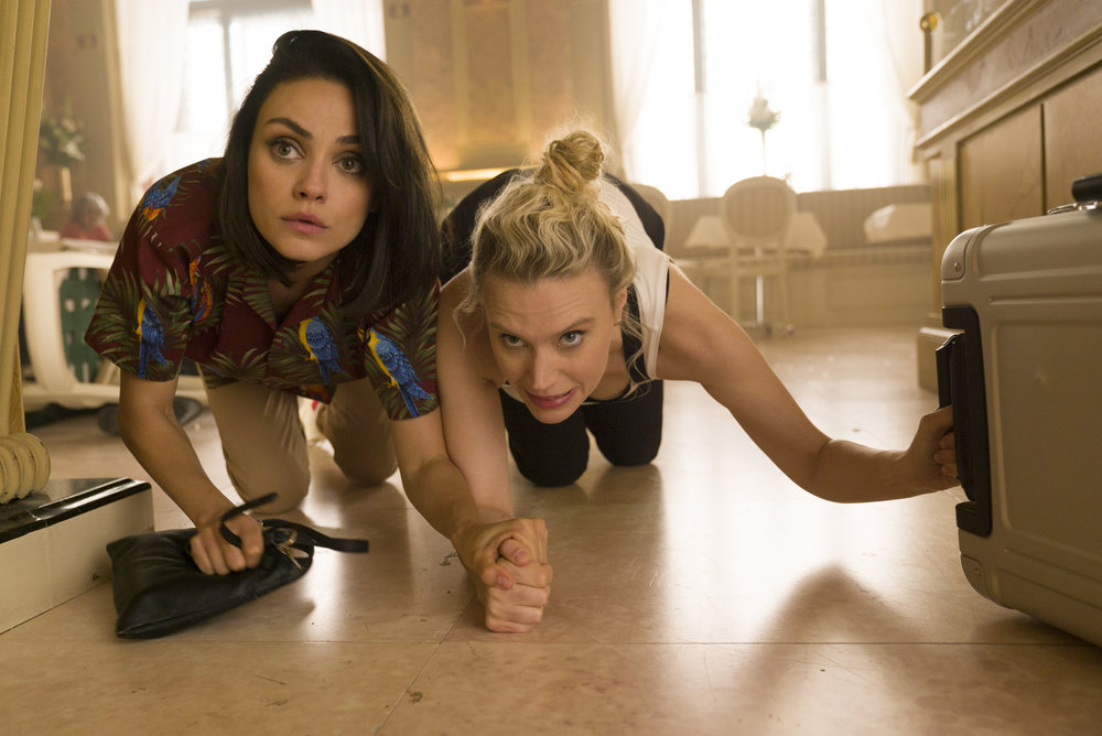"""Friends Audrey (Mila Kunis, left) and Morgan (Kate McKinnon) duck during a shootout in Vienna, in a scene from the action comedy """"The Spy Who Dumped Me."""" (Photo by Hopper Stone, courtesy of Lionsgate)"""