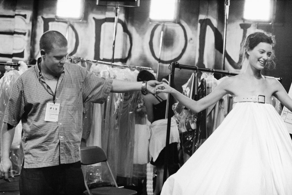 "Fashion designer Alexander McQueen (left) examines the dress worn by model Shalom Harlow before a show, in a moment from the documentary ""McQueen."" (Photo by Ann Ray, courtesy Bleecker Street Films)"