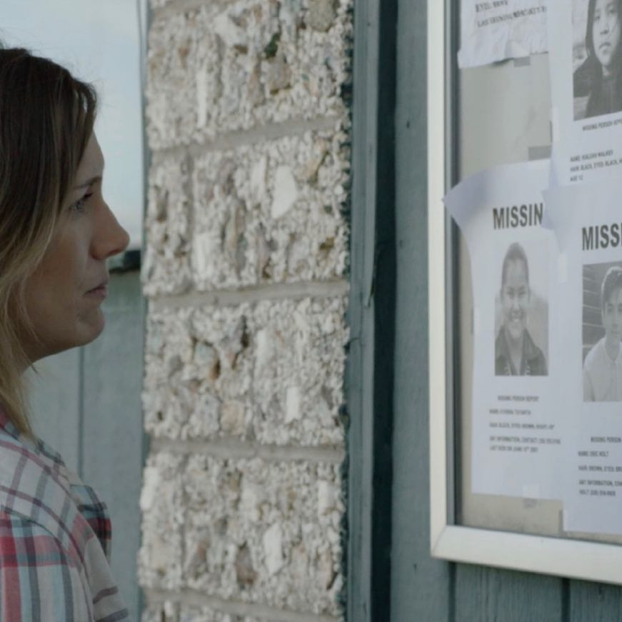 "Ann (Lyndsey Lantz) looks at a board of missing-person flyers, including one for her son, in the suspense thriller ""Lore."" (Photo courtesy Folklore Films)"