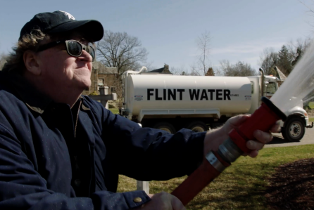 "Michael Moore delivers water from Flint, Mich., to the state's Republican governor, Rick Snyder, in a moment from his latest documentary, ""Fahrenheit 11/9."" (Photo courtesy Briarcliff Entertainment)"