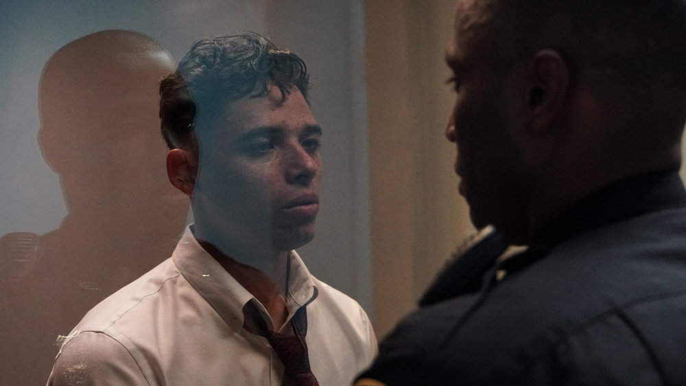 "Manny (Anthony Ramos, left), a young father who took video of a police shooting, finds himself in an interrogation room, being looked over by a policeman, Dennis (John David Washington), in a scene from the drama ""Monsters and Men."" (Photo courtesy MoviePass Films / Neon Films)"