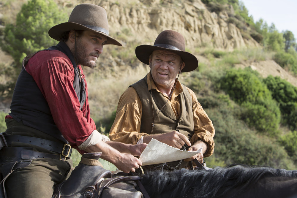 "Assassins Charlie Sisters (Joaquin Phoenix, left) and Eli Sisters (John C. Reilly) are on the trail toward a rendezvous with a detective (Jake Gyllenhaal) and a chemist (Riz Ahmed), in the Western drama ""The Sisters Brothers."" (Photo by Magali Bragard, courtesy of Annapurna Pictures)"