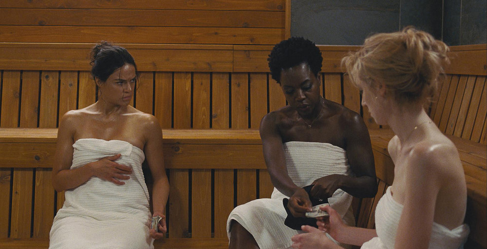 """Linda (Michelle Rodriguez, left), Veronica (Viola Davis, center) and Alice (Elizabeth Debicki) discuss plans for a heist their husbands didn't live to commit, in the crime drama """"Widows."""" (Photo courtesy 20th Century Fox)"""