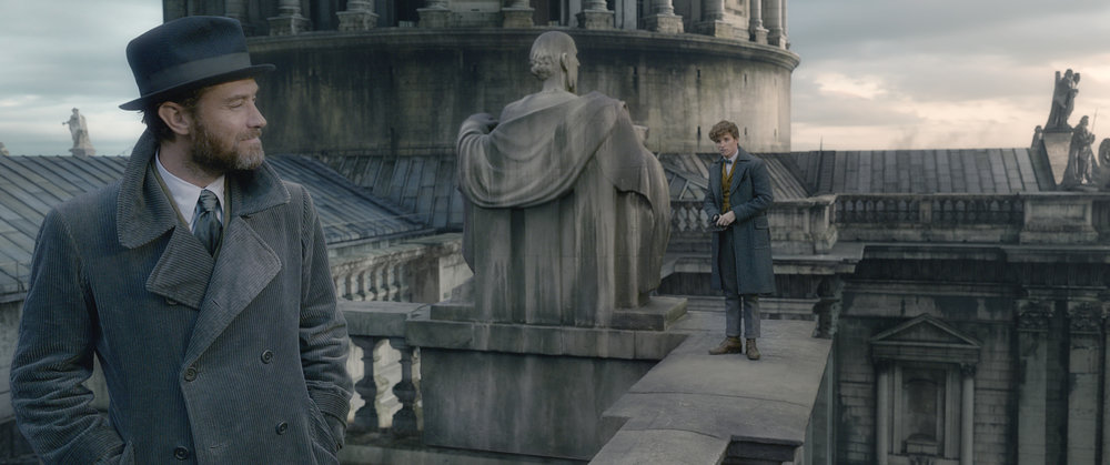 """A younger-than-we're-used-to Albus Dumbledore (Jude Law, left) meets his old student, Newt Scamander (Eddie Redmayne), on a Paris rooftop in """"Fantastic Beasts: The Crimes of Grindelwald,"""" the 10th movie set in J.K. Rowling's Wizarding World. (Photo courtesy Warner Bros. Pictures)"""