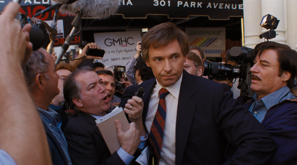 "Presidential candidate Gary Hart (Hugh Jackman, center) is swarmed by reporters and TV crews after a scandal, in a scene from the political drama ""The Front Runner."" (Photo courtesy Columbia Pictures)"