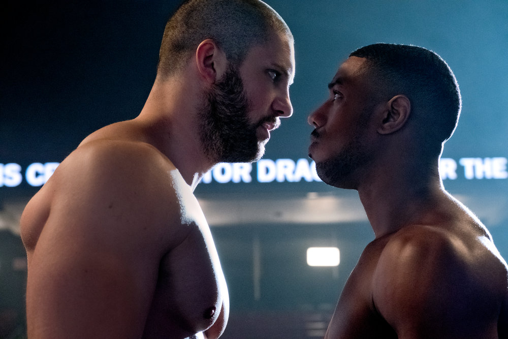 """Adonis Creed Johnson (Michael B. Jordan, right) stares down Viktor Drago (Florian """"Big Nasty"""" Munteanu), the son of the boxer who killed Adonis' father in the ring, in a scene from """"Creed II."""" (Photo by Barry Wetcher, courtesy of Metro Goldwyn Mayer Pictures / Warner Bros. Pictures)"""