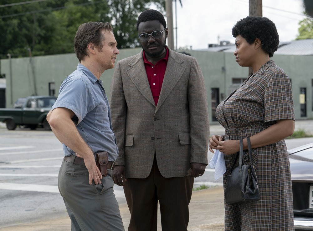 """C.P. Ellis (Sam Rockwell, left), a local leader of the Ku Klux Klan, talks to civil rights activist Ann Atwater (Taraji P. Henson, right) and negotiator Bill Riddick (Babou Ceesay, center) over school integration in Durham, N.C., in 1971, depicted in the drama """"The Best of Enemies."""" (Photo by Annette Brown, courtesy STX Films)"""