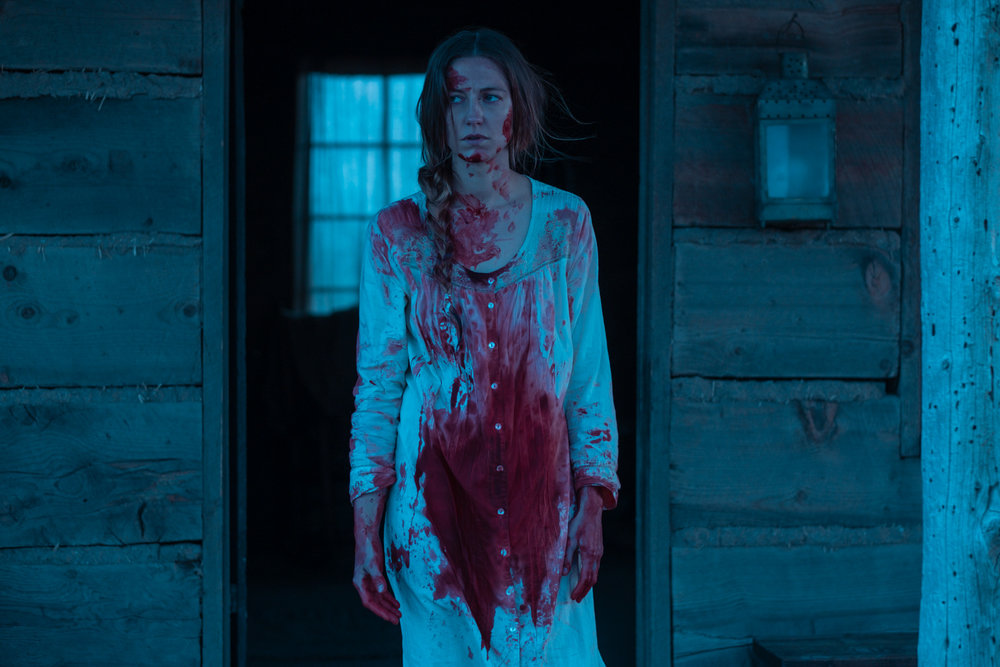 """Lizzy Macklin (Caitlin Gerard) emerges from a bloody attempt to save a neighbor's unborn baby, in a scene from the Western horror thriller """"The Wind."""" (Photo courtesy IFC Films)"""