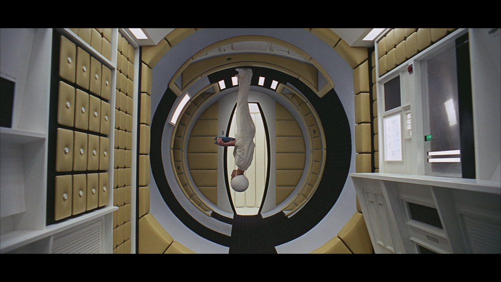 A stewardess running errands in a space station appears to be positioned upside down.  Great colors and center composition.