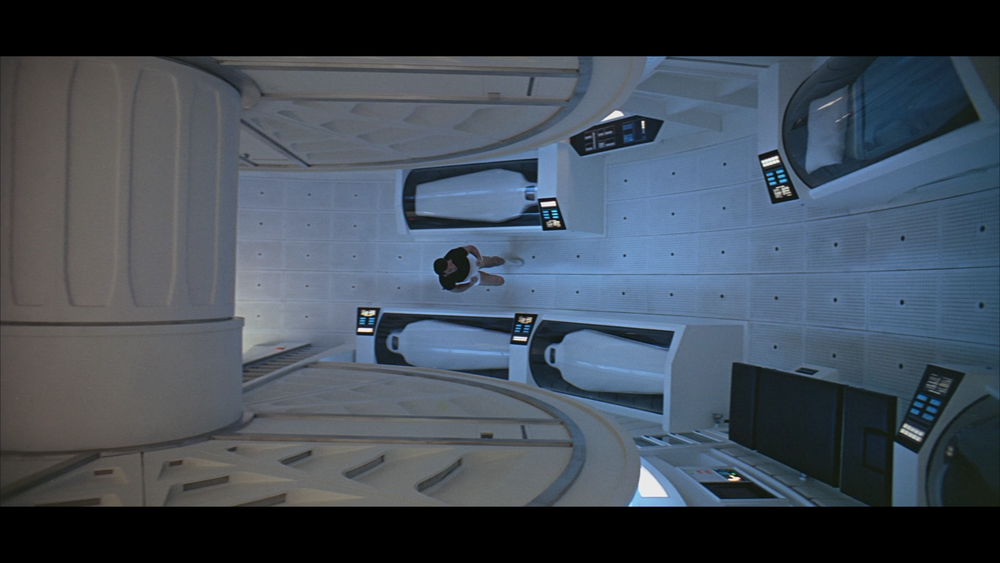 Dr. Frank Poole, played by Gary Lockwood, jogs in a circular room while aboard  Discovery One.   This scene is a great example of the aspect ratio, 2.2:1, working to its advantage. The camera pans from left to right while following Poole. Once he reaches the right most edge of the frame, the camera reverts back to the original, left position and follows Poole rightward again. This is a great way of illustrating the dimensions of the  Discover One's  main room.  Here is an panoramic view (first and third screenshots) of the room.