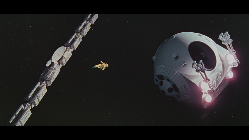 Frank Poole floats towards the  Discovery One,  attempting to put back a communication device that HAL had deemed was malfunctioned.  The framing and composition of the shot is well done and adds to the storytelling components of the scene. Poole looks tiny in comparison to the pod, which ends up being the *spoiler alert* weapon of his demise.