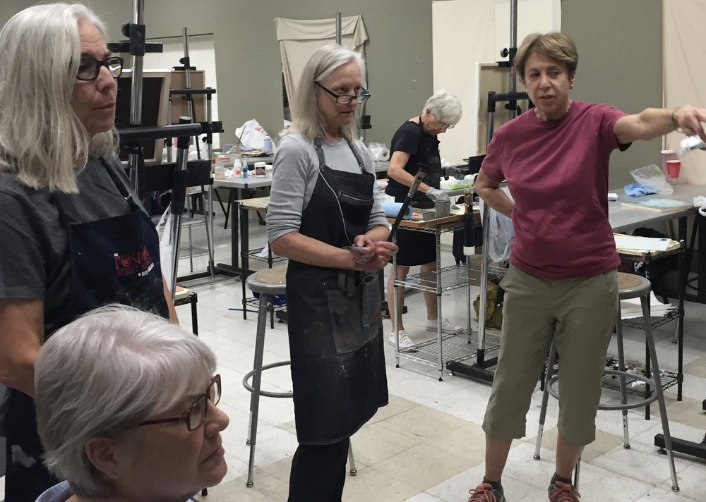 students and instructor marianne mitchell discuss an oil painting