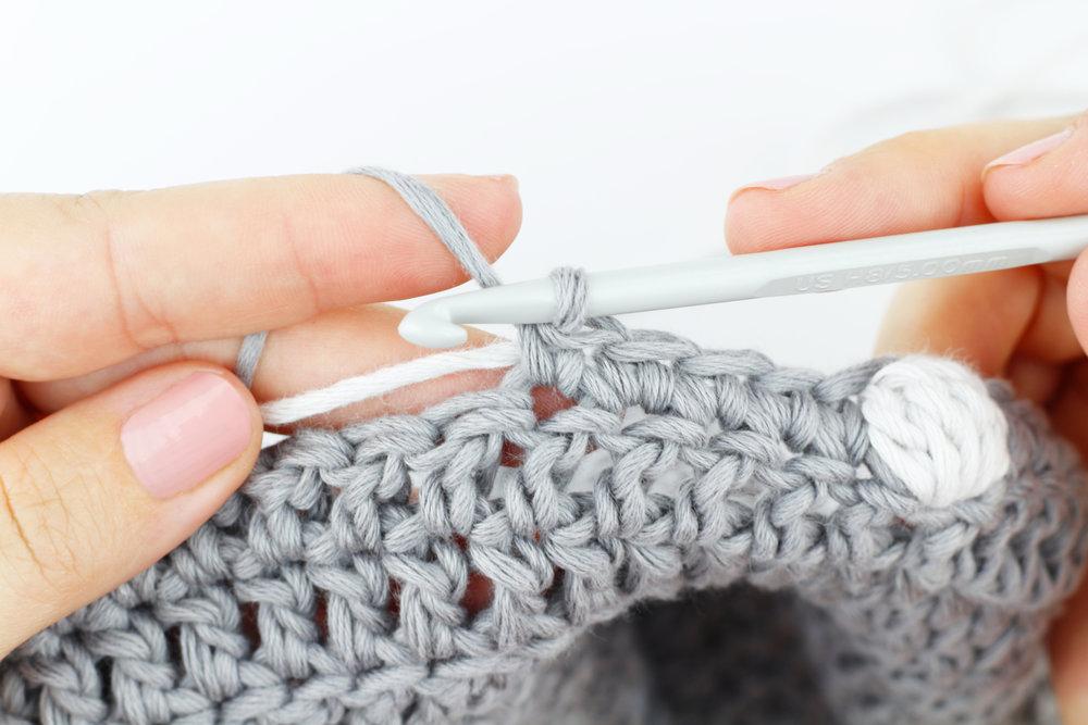 2  Continúa tejiendo y ocultando el color que no estés usando entre las puntadas.