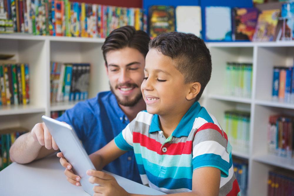 bigstock-Teacher-and-school-kid-using-d-139955609.jpg