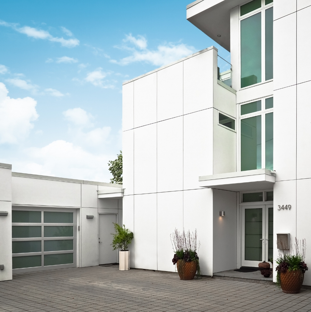 Modern all white home exterior with garage against a blue sky