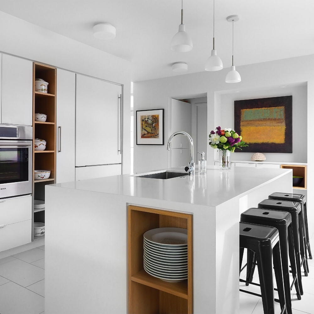 modern all white kitchen with black stools and large paintings on the walls