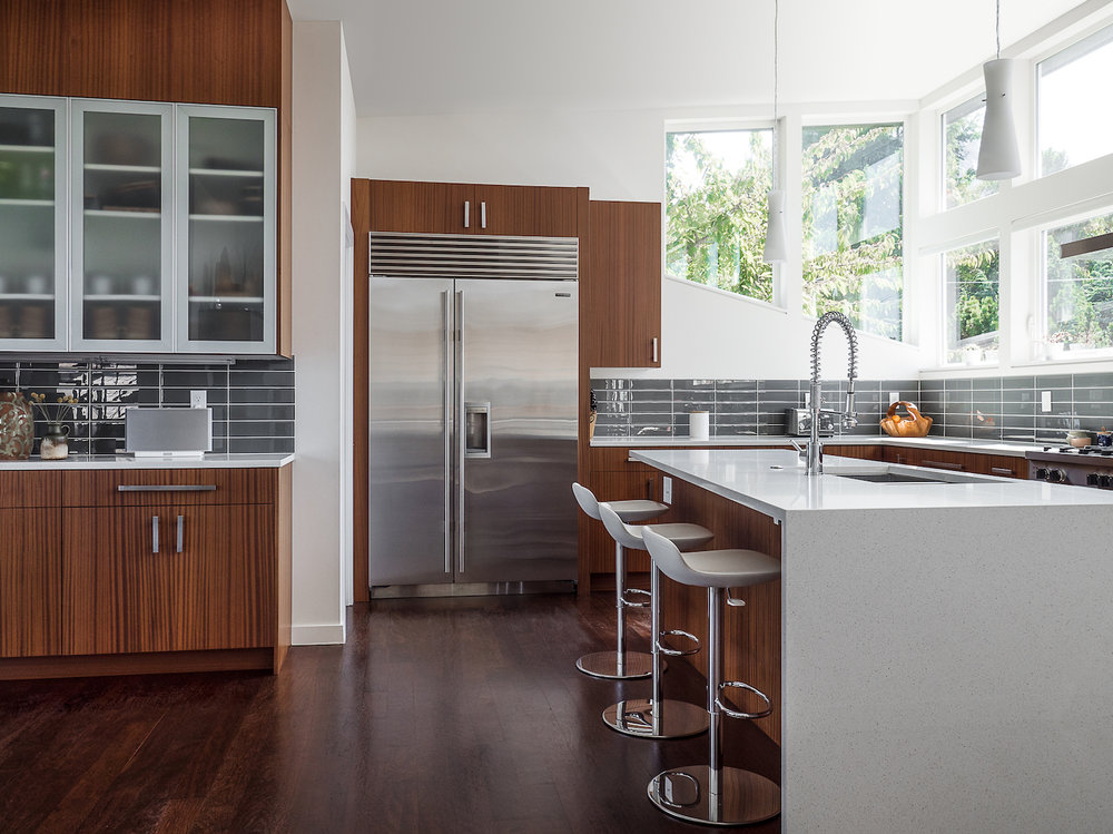 modern kitchen with island in shades of white with dark wood accents