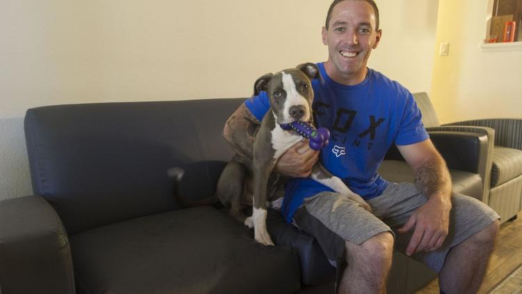 Ryan poses with his foster dog in his first apartment.