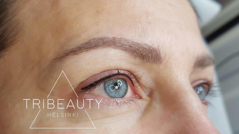 Valmis ja parantunut kulmapigmentointi karvatekniikalla kahden käsittelyn jälkeen. Asiakas toivoi kulmiinsa boheemia lookia eikä häntä haitannut hajakarvojen olemassa olo. Kuvassa myös eyeliner pigmentointi yläluomella jälkipigmentoinnin jälkeen.