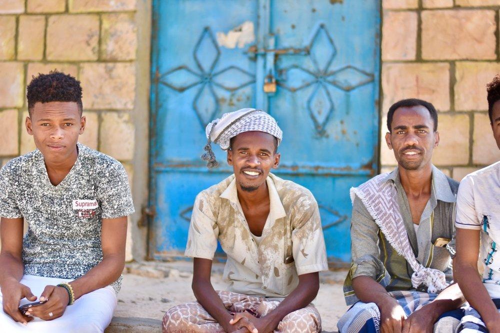 Yemeni men sitting on a porch, smiling