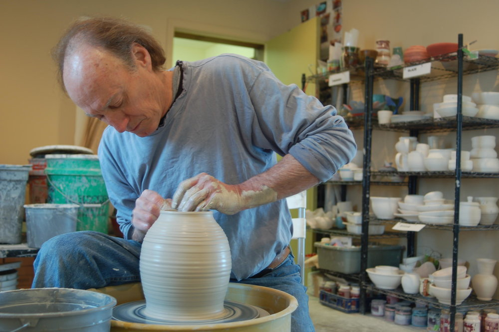 """phil wilson - I simply want to make good pots. By that I mean functionally elegant and interesting, beautiful to look at and comfortable in everyday use. I am guided by an interest in the entire spectrum of pottery traditions and try in my own work to arrive at forms that are both classic and thoroughly functional.I like to work on groups of pots. There is always some particular form I'm interested in, but it's much more interesting to play around with that form than try to """"perfect"""" it. So each group is a series of variations that illustrate possibilities, in the same way that a bowl of pears gives you an idea of what a pear looks like.While each piece begins on the wheel, I alter some of these round forms and use parts of them to construct others with a very different two or four-sided character.The smooth porcelain surfaces are activated with patterns of texture from throwing marks on the wheel, impressions in the wet clay and carving into the leather-hard clay. These textures are accentuated and softened by subtle glazes: cool, glossy celadon and warm, semi-matte black. All glazes are non-toxic, microwave and dishwasher safe, and versatile in any environment."""
