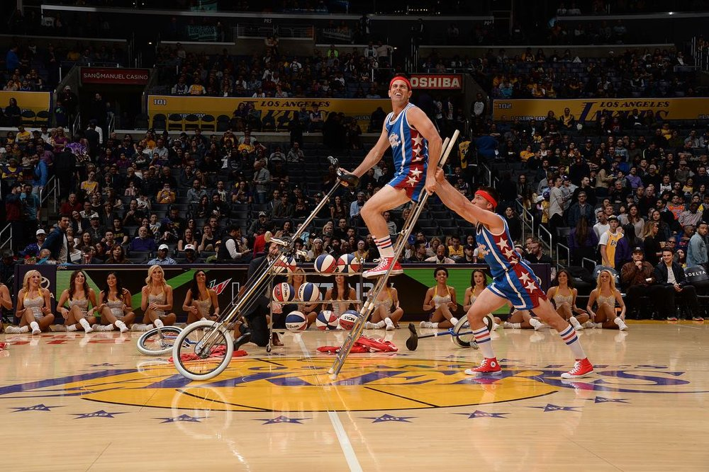 LA Lakers halftime show Jon pushing Mark up on ladder so he can mount his tall unicycle