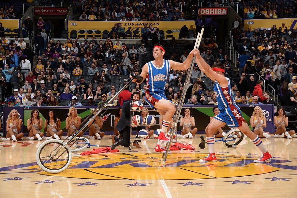 LA Lakers halftime show Jon pushing Mark up on a ladder so he can mount his tall unicycle