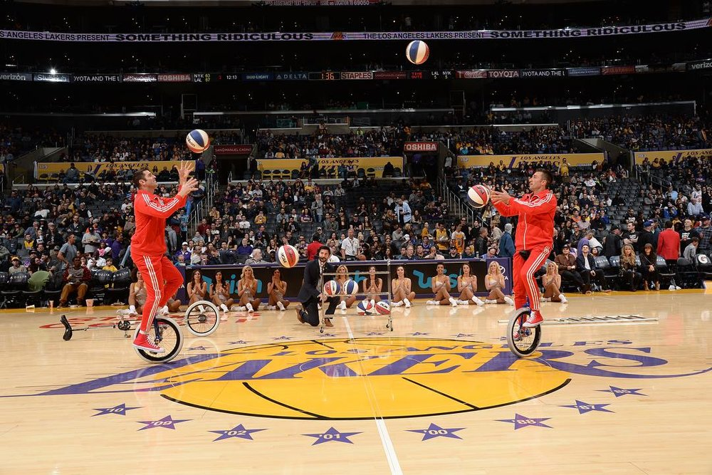LA Lakers halftime show Jon and Mark on short unicycles playing catch with basketballs