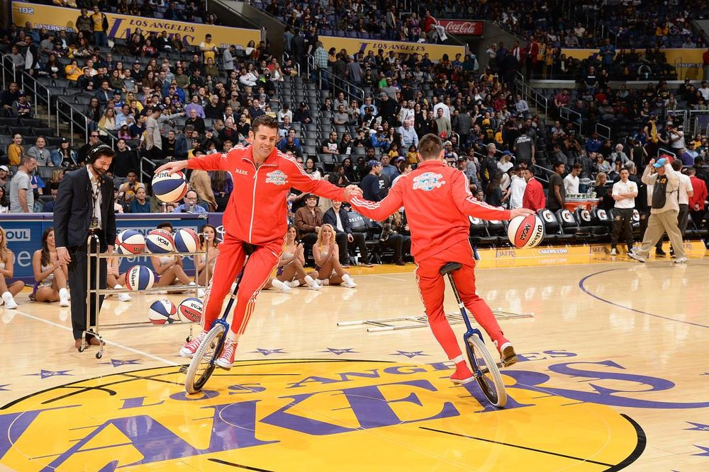 LA Lakers halftime show Jon and Mark on short unicycles dribbling basketballs in a circle