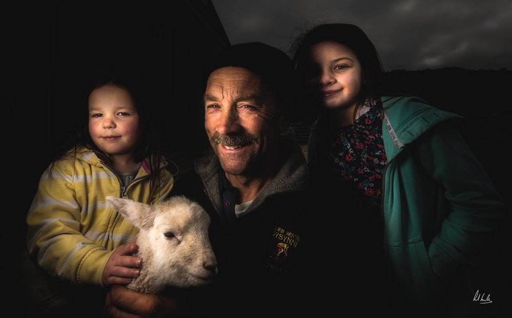 Lambing Time - A visit to Tom and Rhian's farm ended with this photograph of Tom with his grandchildren. The lamb in the image had been abandoned by its mother and was being hand reared before another ewe could be found to adopted it. The image was taken using a lastolite attached to a Nikon SB-910. Although the photograph was taken in bright sunlight the effect of using the flash created a lovely moody feel to the image.