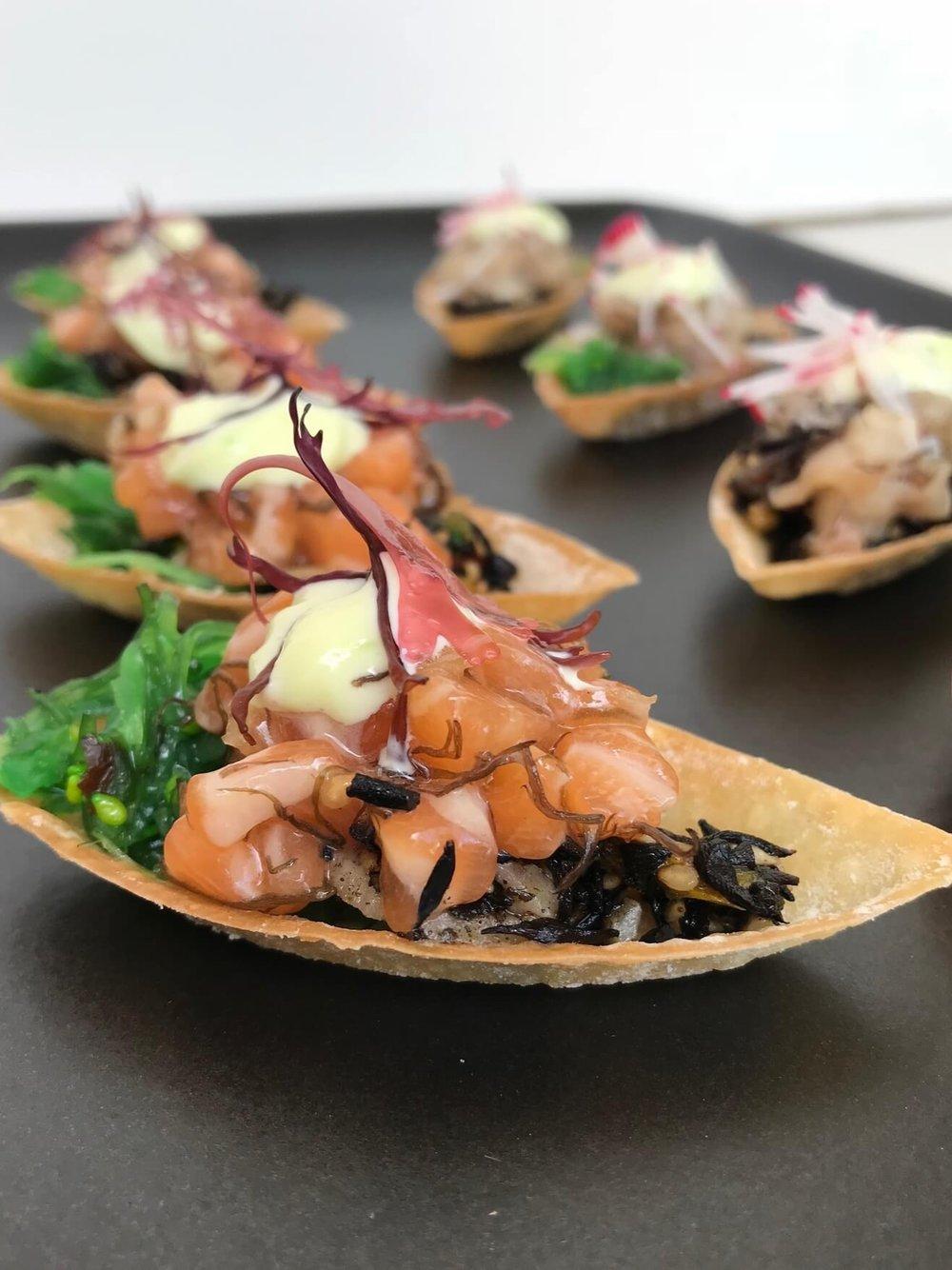Salmon and Hamachi Poke Boats - Fresh salmon and hamachi poke with hijiki and wakame saladServed in wonton boats and garnished with dulse, radish, and wasabi mayo