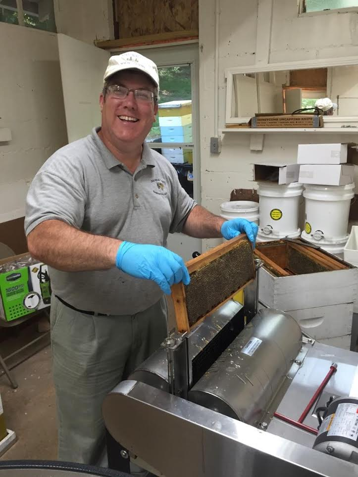 Allen Blanton, President of the Haywood County Beekeepers Association, using the chain uncapping device on a frame of his delicious honey.
