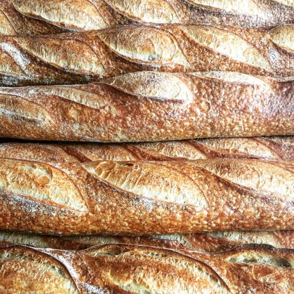 Baguette - Inspired by the classic French Baguette, baked with European style (lower gluten) flour, our rendition also contains a small percentage of local corn hence giving it a slightly gold hue. As a result of high hydration and slow fermentation, our baguette has an longer shelf life than most.22 x 2.5 x 2.0in