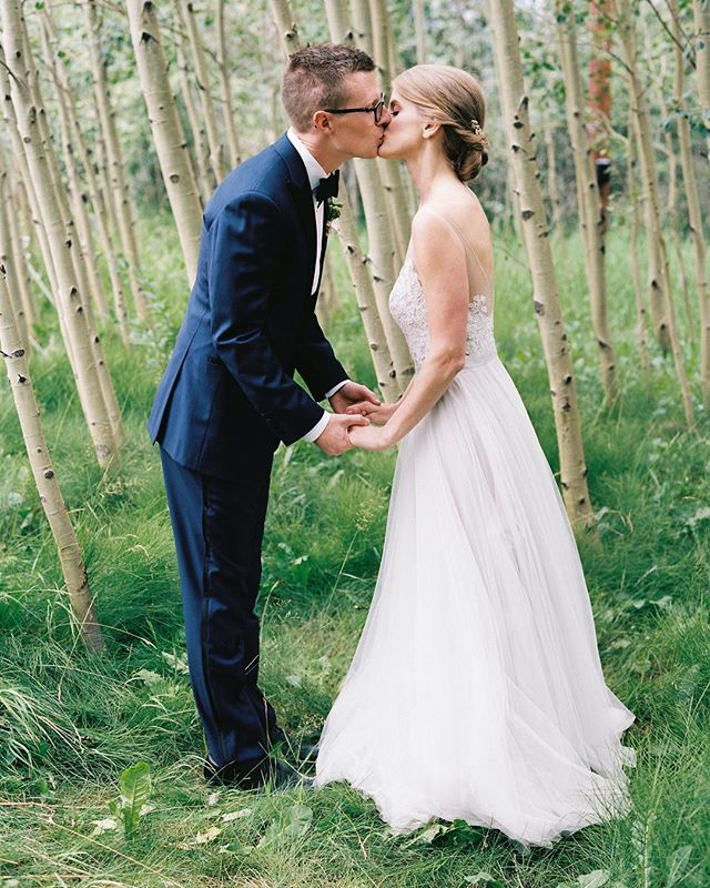 A kiss in the trees. Planner @avintageaffaircolorado | florals @parkfloraldesign | makeup @lizweg | scabs @photovisionprints #filmphotographer #outdoorwedding