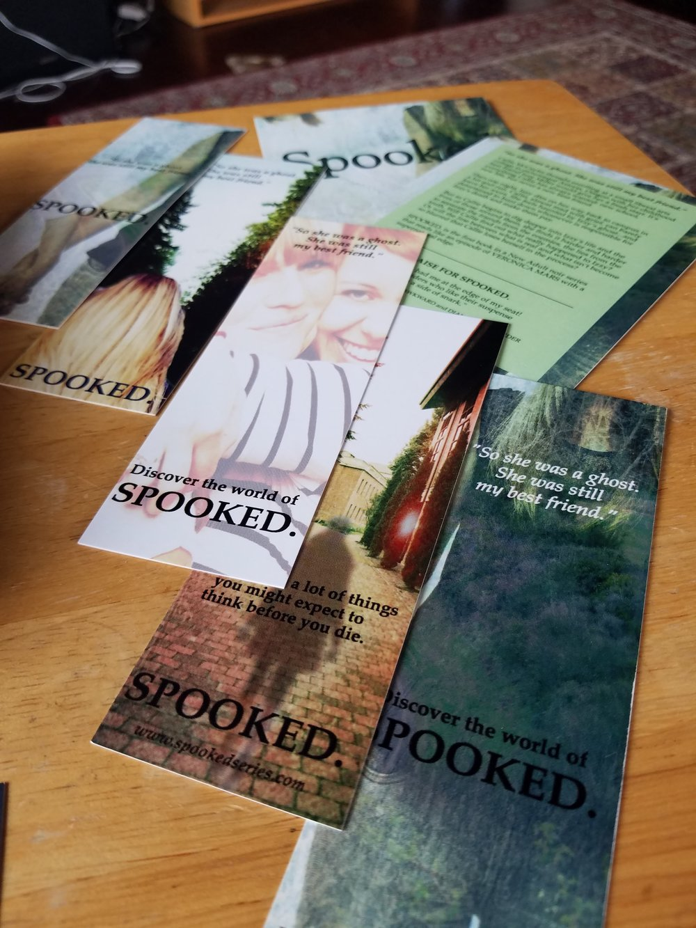 A photo of just some of the available SPOOKED. swag! Bookmarks and postcards, yay!