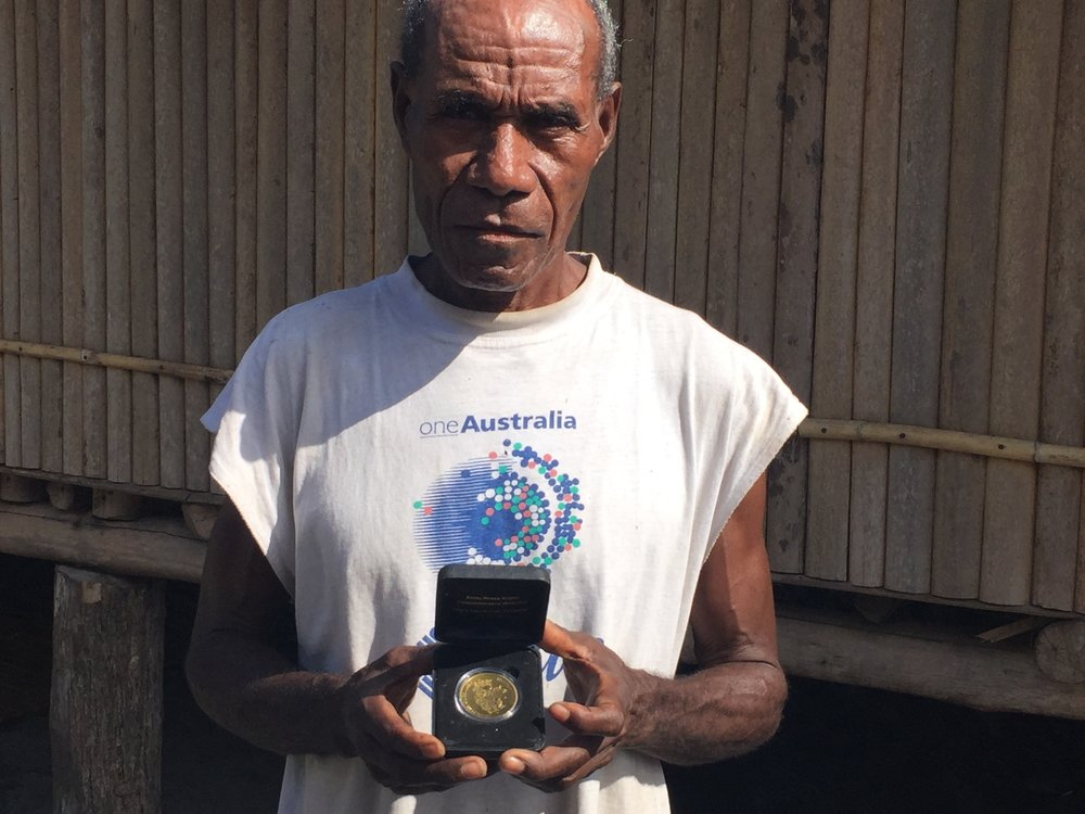 Mr Elking Doroda holds the Fuzzy Wuzzy Commemorative Medallion awarded to his father for service as a carrier during the Second World War. New Buna village, Oro Province, Papua New Guinea, 2017. Photo: Dr Victoria Stead