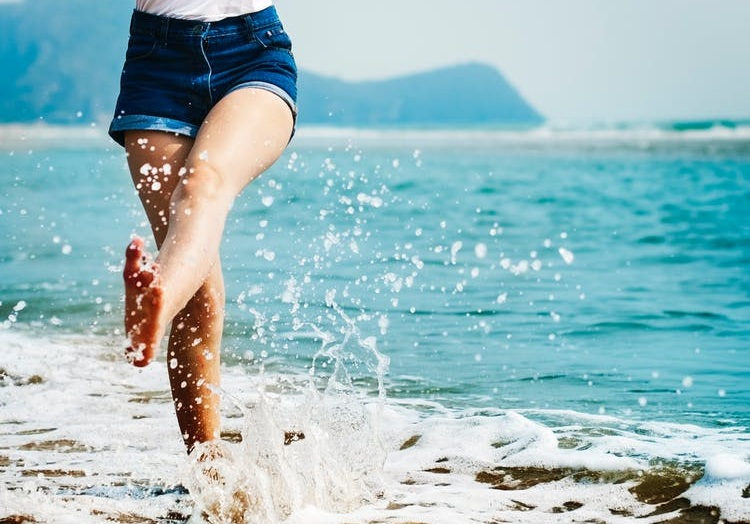 Lady in denim shorts walking in the sea - ME, CFS and Fibromyalgia Support