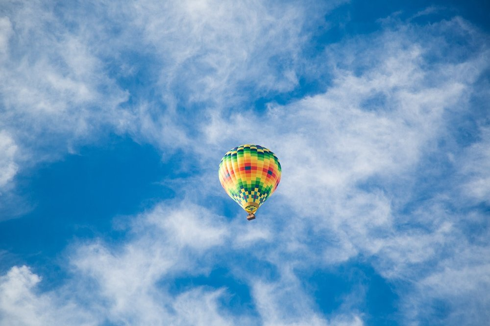A colourful hot air balloon floats across a blue sky with fluffy clouds - Stress Management
