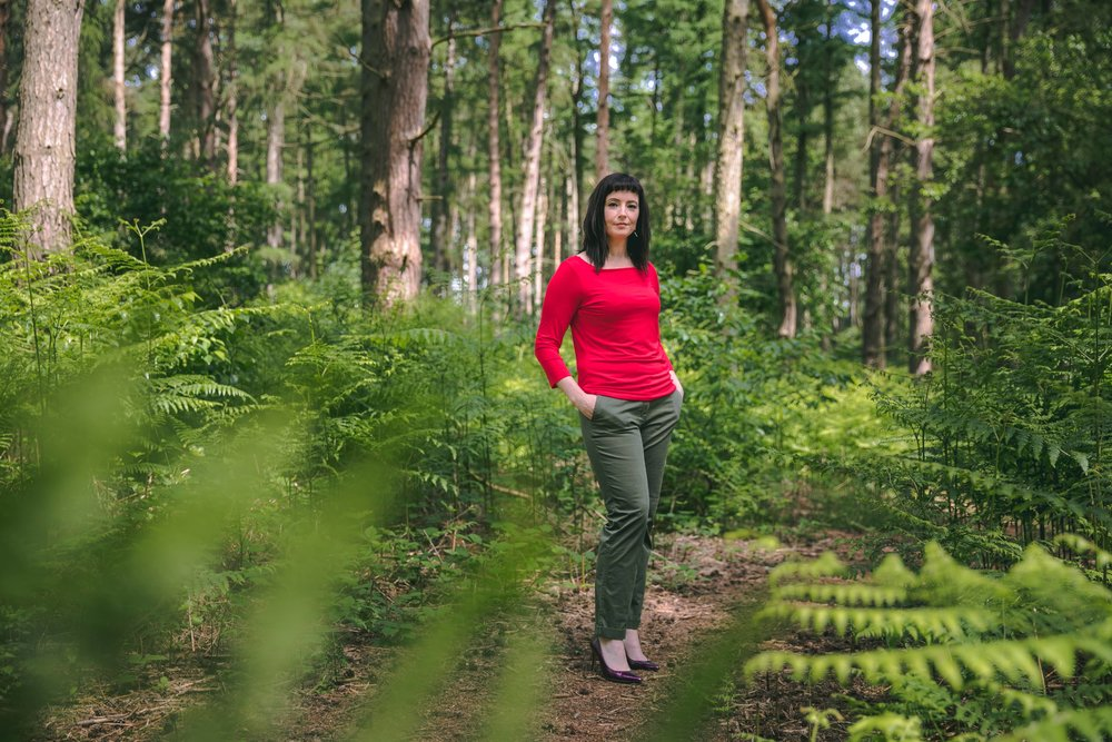 Anne Bryant in a forest with a red top on - Myalgic Encephalomyelitis Practitioner