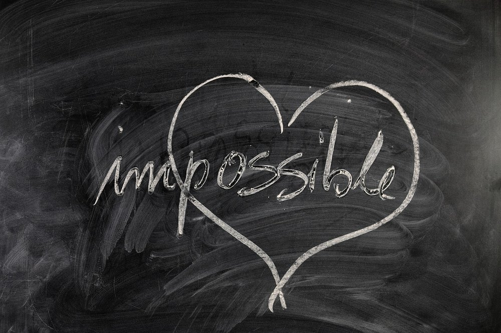 a chalkboard with the word impossible written on it. a heart is drawn around the possible - how coaching works - making the impossible possible