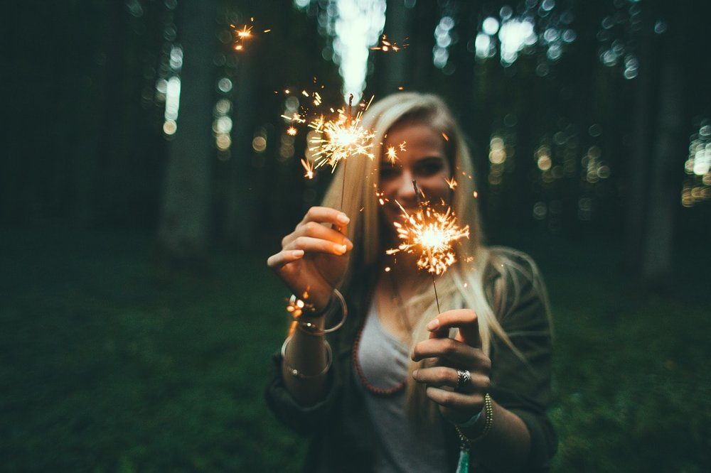 a blonde woman holding two sparklers and smiling - how coaching works