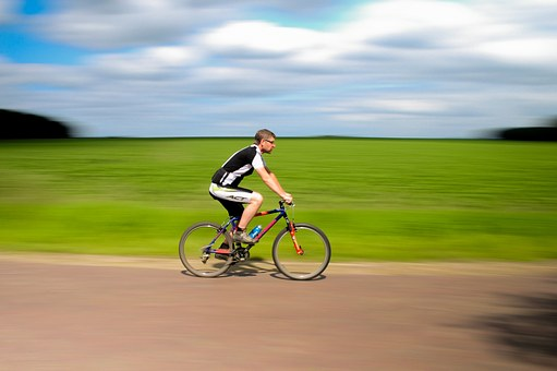 man riding a bicycle against a summer field background - how smooth is your wheel of life