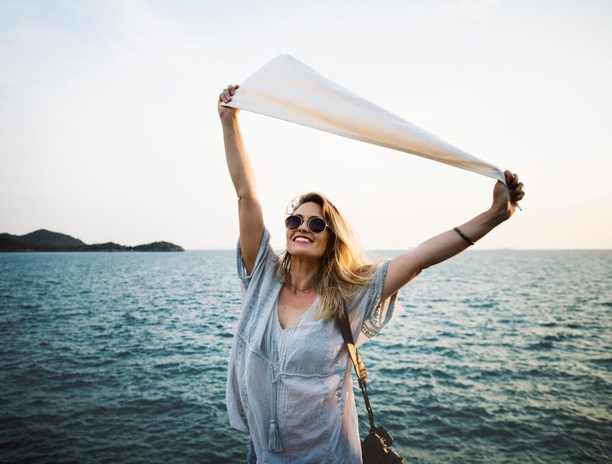 a smiling woman wearing sunglasses joyfully raises a flag above her head against a seascape background - Coaching for fulfillment