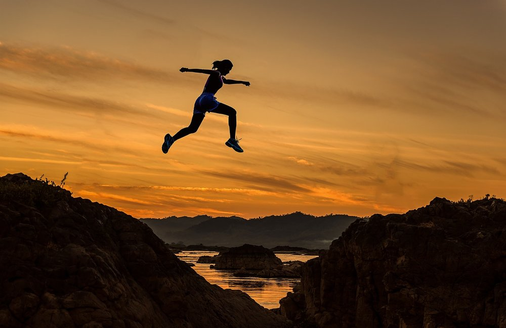 a woman leaps across a gap in the mountains at sunset-how to lose weight successfully