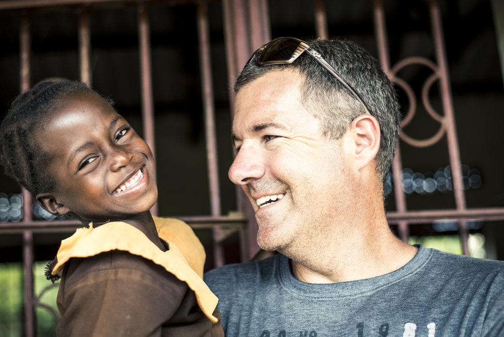 Director, Steve Denney, with village child in Uganda