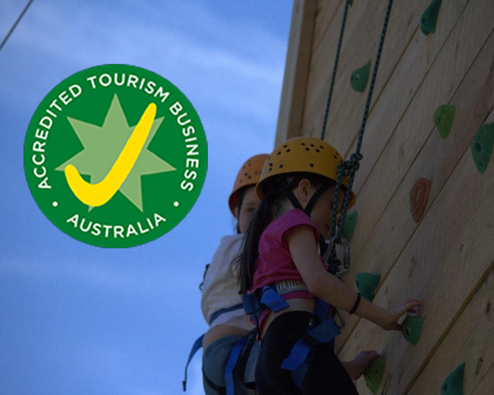 Girls on Abseil Tower with Accreditation Logo.png