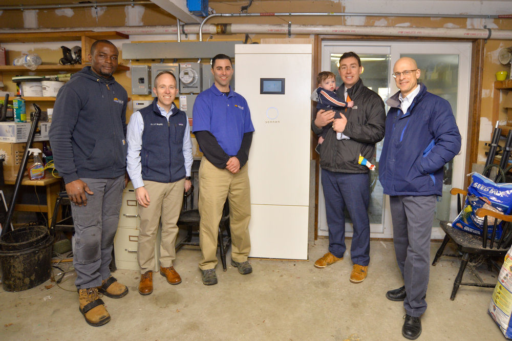From left to right: Joe Eneh, Mark Sylvia, Brad Stoler, Senator Ryan Fattman with son Grant, and homeowner Robert Johnston with a Sonnen Eco10 Battery Backup System installed by Rayah Solar.
