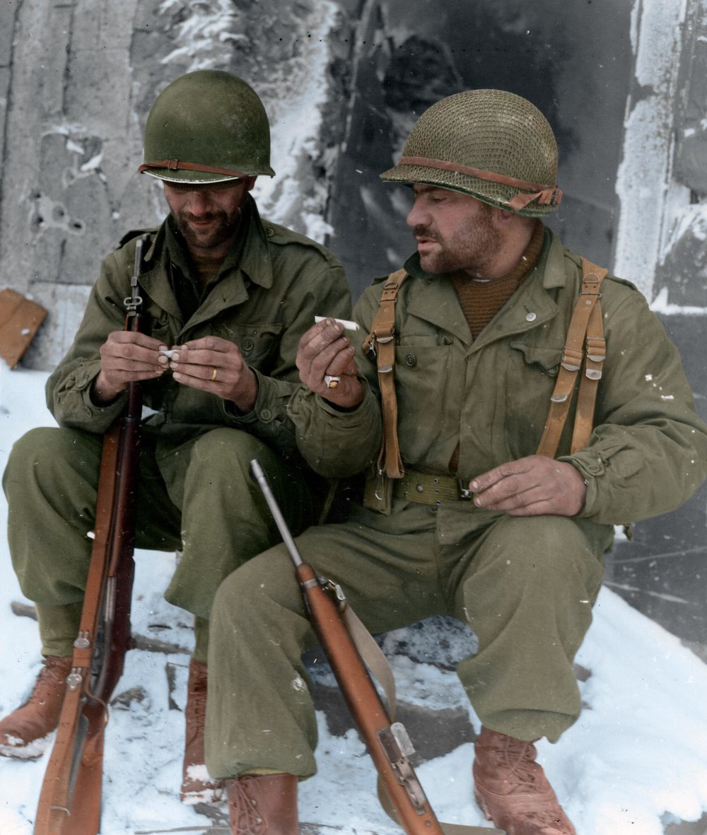 Two riflemen from the 317th Infantry Regiment, 80th Infantry Division, take a moment to roll their own cigarettes in Goesdorf after 27 days of fighting