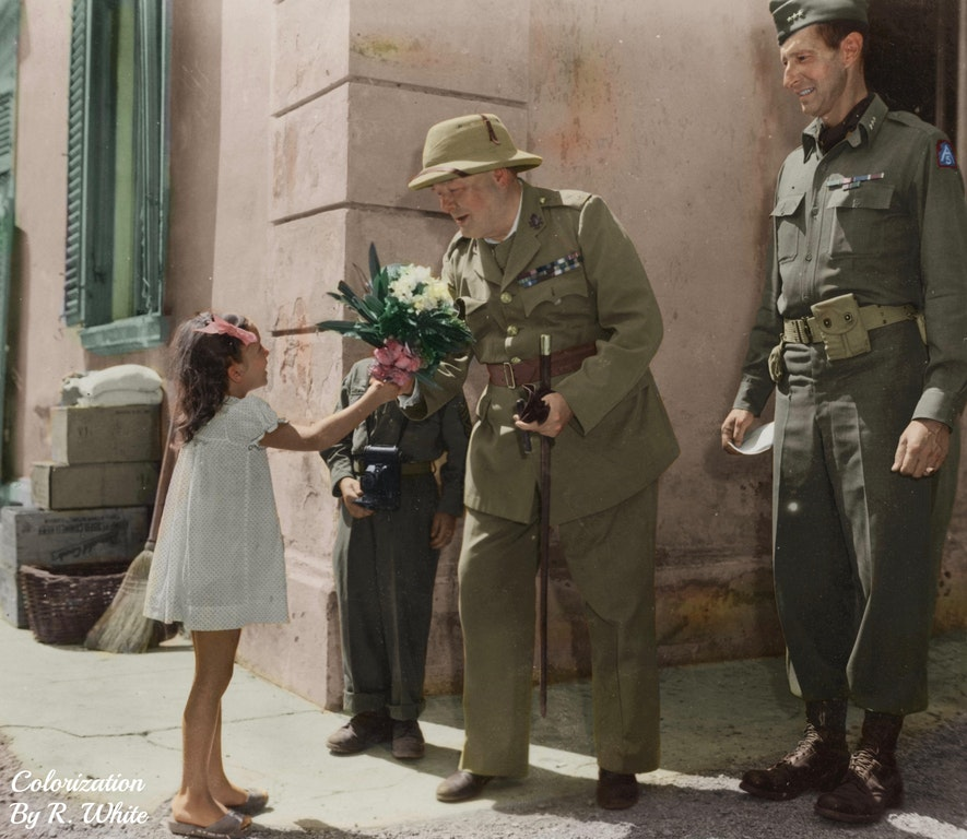 Winston Churchill and Lieutenant General Mark Clark of the US Army are greeted with flowers by a child in Castiglioncello, Italy, 19 August 1944
